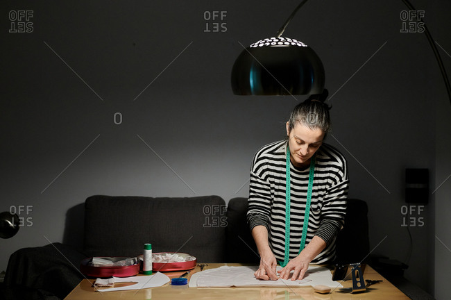 Focused female designer in casual clothes working with fabric in light of modern lamp at wooden table near sofa at home