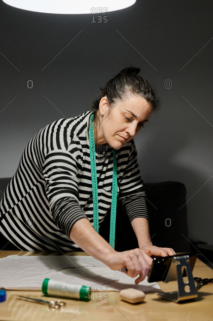 Focused female designer in casual clothes standing near table with tools and fabric while using smartphone to watch a tutorial during work at home