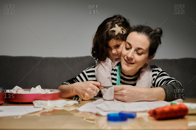 Loving adult woman with daughter sitting at wooden table and cutting pieces of fabric with scissors while creating new dress at home