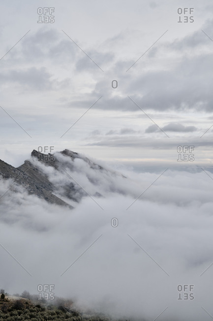 Amazing view of mountain peaks covered with fog and clouds in overcast weather