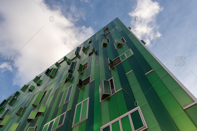 November 27, 2019: From below view of facade of modern green building with windows and panels on wall on sunny day in city