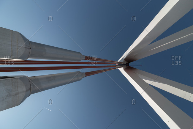 February 24, 2020: From below of contemporary industrial bridge with metallic cables of suspension construction attached to concrete pillars under blue sky