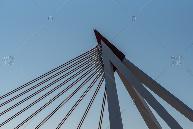 February 24, 2020: Low angle of construction of modern bridge with metal and concrete pillars and cables on sunny day in city