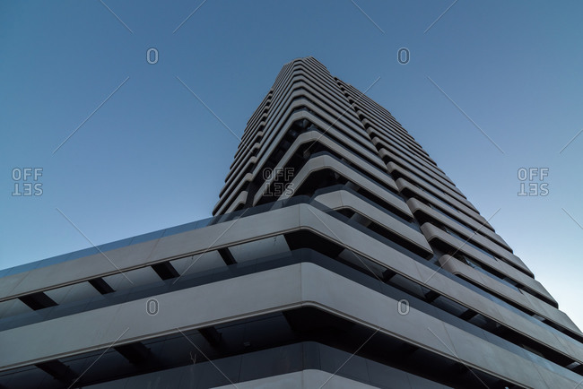 March 8, 2020: From below of modern high concrete building facade with rows of balconies located in city on cloudless day