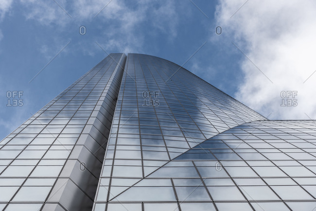 November 27, 2019: Low angle of contemporary high rise building facade with glass exterior under white cloudy sky in modern city district