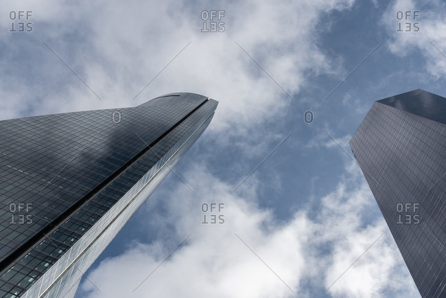 November 27, 2019: Low angle of contemporary high rise buildings facade with glass exterior under white cloudy sky in modern city district