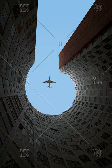 March 8, 2020: From below of black and white aircraft flying high over modern building with round yard in in city