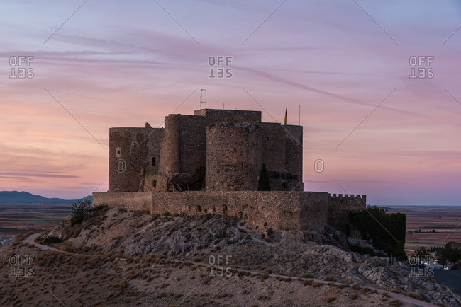 Old castle with shabby stone walls located against cloudy sundown sky in nature