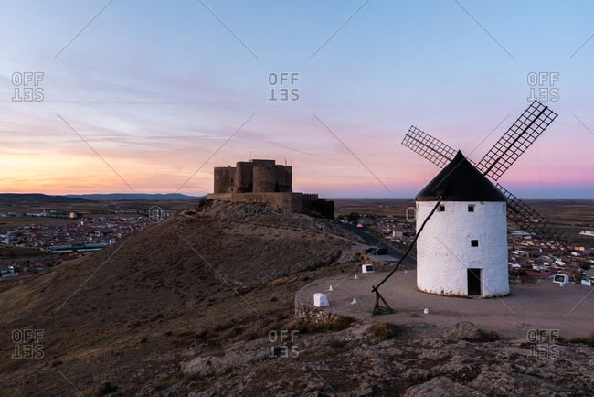Aged windmill located on rocky cliff near medieval castle against cloudy sundown sky in countryside