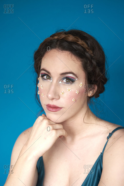 Portrait of charming tender lady with makeup and small flowers on cheeks touching chin while resting near blue wall in light studio and looking at camera