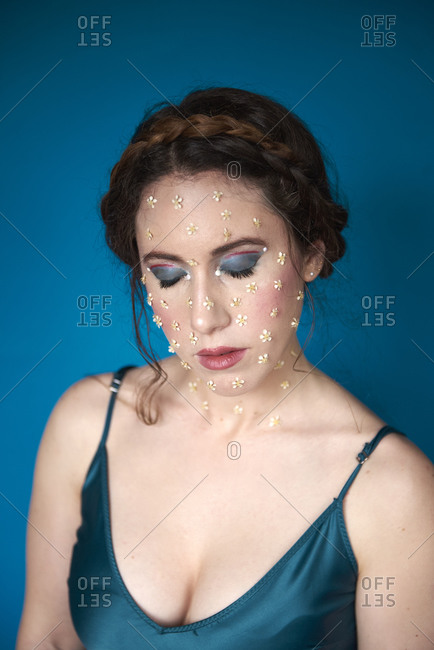 Portrait of charming tender lady with makeup and small flowers on cheeks touching chin while resting near blue wall in light studio with closed eyes