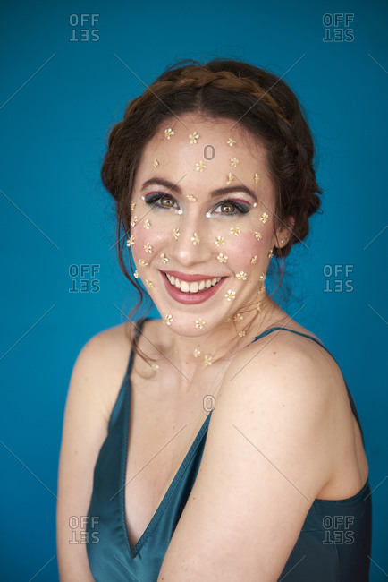 Portrait of charming cheerful woman with makeup and small flowers on cheeks touching chin while resting near blue wall in light studio and looking at camera