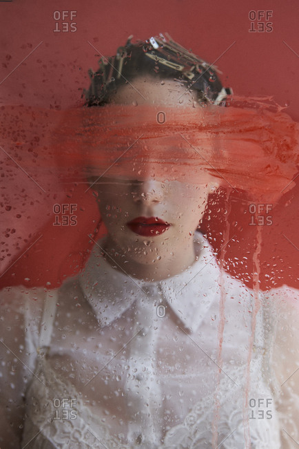 Young emotionless female model with red lips standing behind wet glass with smeared red paint against red background