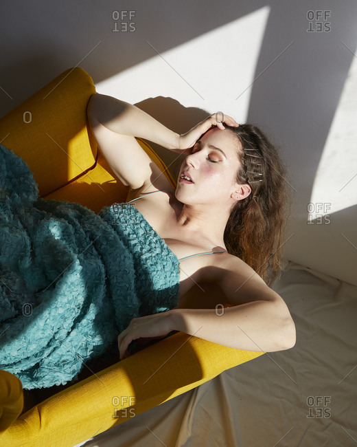 Expressive suffering female in creative green dress lying with closed eyes in bright yellow chair in sunlight spots inside studio with white wall and crumpled fabric on floor