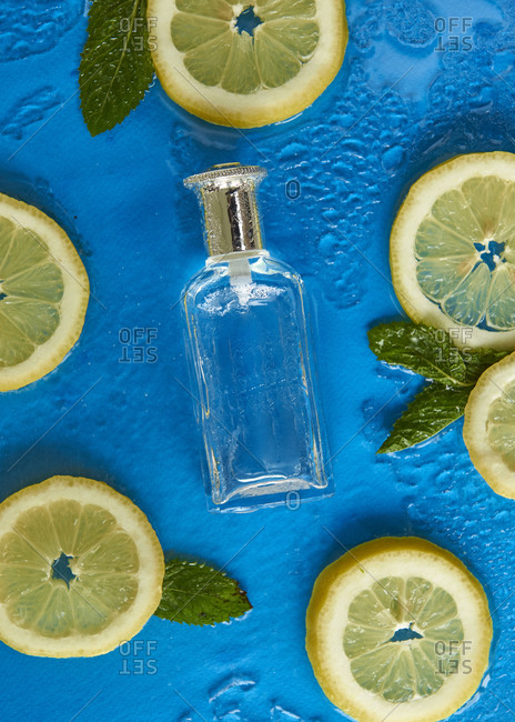Top view of empty glass bottle surrounded by fresh lemon slices with mint leaves on blue background covered by clear water drops