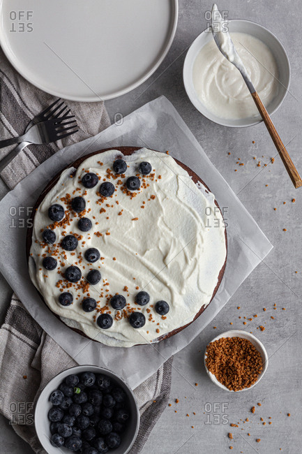 From above view of plate with tasty homemade chocolate cake decorated with white cream and blueberries placed on table in kitchen