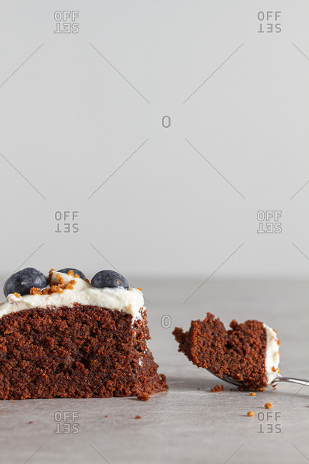 Slice of homemade chocolate sponge cake topped with fresh whipped cream and whole blueberries placed on table in light kitchen