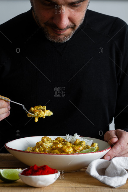Male in casual wear sitting at table in kitchen and taking piece of spicy curry made of prawns and mushrooms and served with rice and lime slices