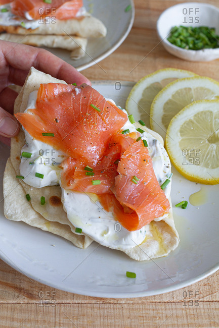 High angle of crop person having lunch and taking flatbread with sour cream and salmon slice garnished with green onion and lemon