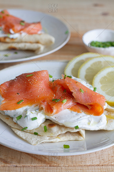 From above of delicious flatbread pieces with sour cream and salmon fillet garnished with chopped green onion placed on wooden table