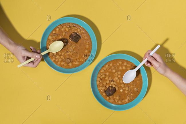 Top view of two hands with Callos dishes over yellow background