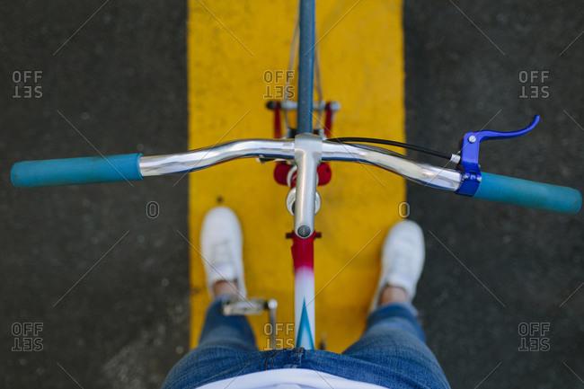 Top view of a fixie bike's handlebar over a crosswalk