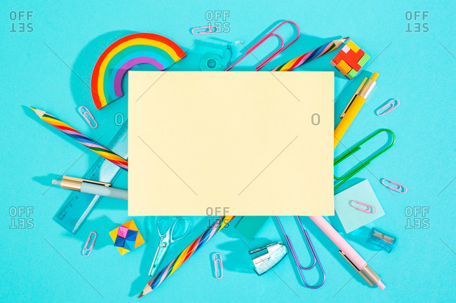 Top view of colorful school supplies with a blank paper for mock up or text.