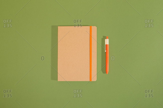 Top view of a minimal composition of recycled notebook and pencil with green background.