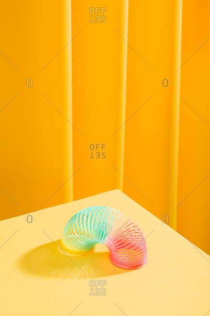 Abstract composition of a colorful toy over a yellow table