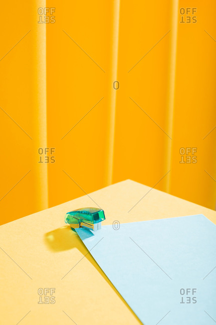 Close-up view of blue stapler with papers over a yellow table
