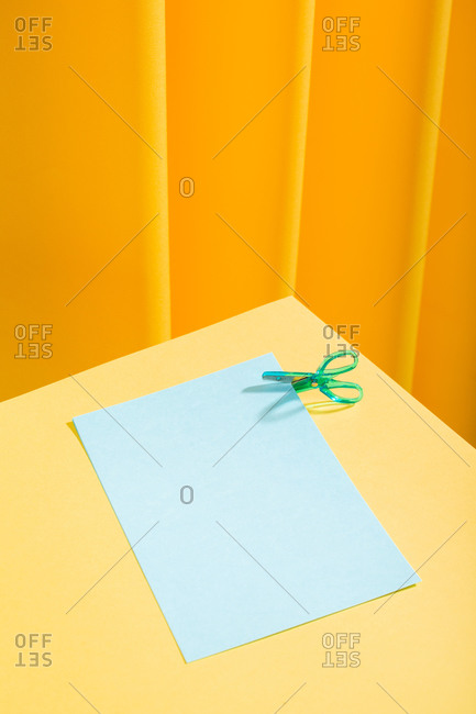 Blue little scissor cutting blue papers over a yellow table