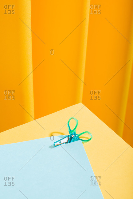Close-up view of blue tiny scissor cutting a blue paper over a yellow table