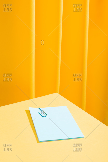 Front view of a minimal composition of a blue paper with a blue paperclip over a yellow table.