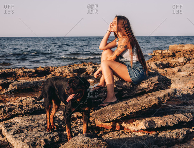 Side view of trendy tattooed woman looking away while sitting on stone with Rottweiler dog while spending time on rocky seashore