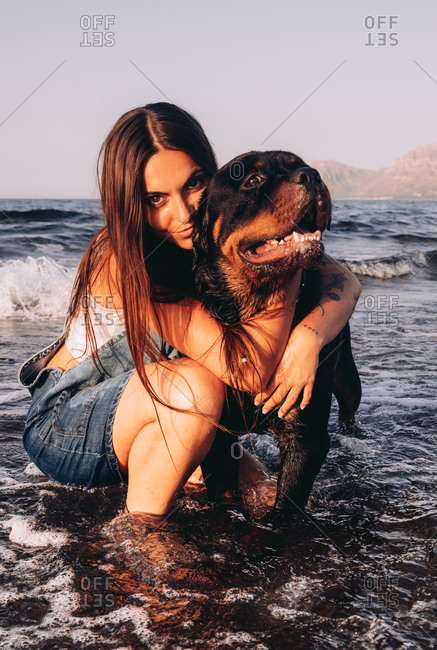 Happy young woman in casual clothes crouched down in water on seashore with big black dog and looking at camera while spending time in evening