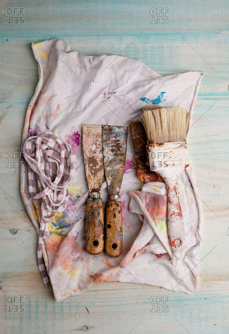 From above of shabby paintbrushes and metal scrapers placed on stained napkin