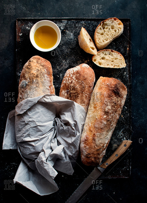 Ciabatta bread on rustic board near olive oil and knife with bread slices on dark background