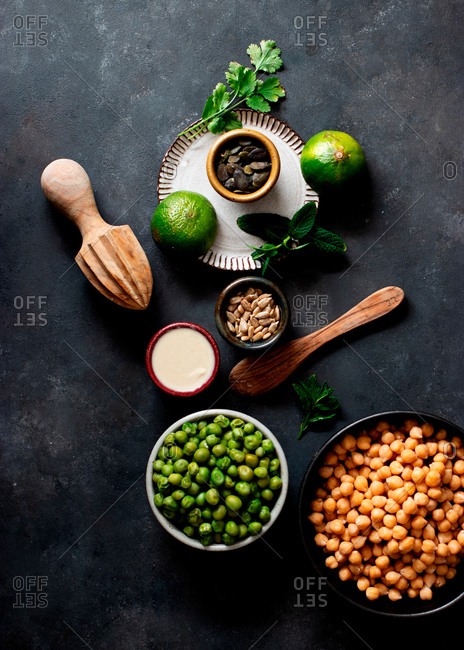 From above chickpeas and green peas placed on a bowl near crackers on dark background