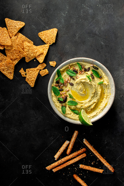From above hummus peas placed on a bowl near crackers on dark background