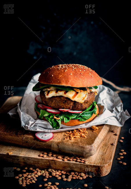 Lentils vegan hamburgers placed on wooden board on dark background