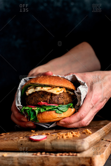 Cropped unrecognizable person holding delicious vegan lentils hamburgers placed on wooden board on dark background