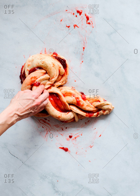From above cropped unrecognizable person hands making fresh strawberry brioche on a kitchen white modern marble table
