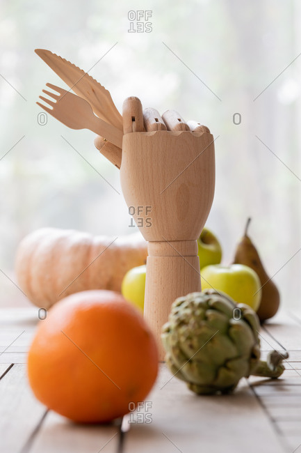 Creative wooden hand with fork and knife placed on table with ripe fruits and vegetables