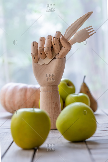 Wooden hand with knife and fork placed on table with fresh fruits and vegetables for nutritious diet