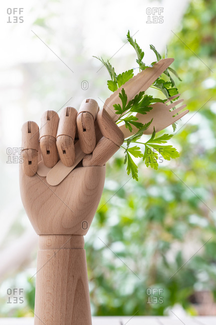 Creative mannequin hand with disposable fork and knife garnished with sprig of green parsley placed on table in garden