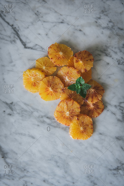 Top view of fresh citrus slices arranged on dish with orange peel and placed on table in kitchen