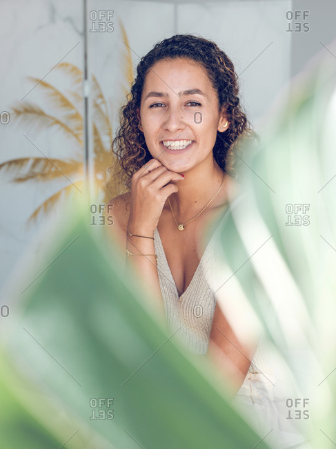 Pretty young woman with curly hair cheerfully smiling and looking at camera while standing in stylish room
