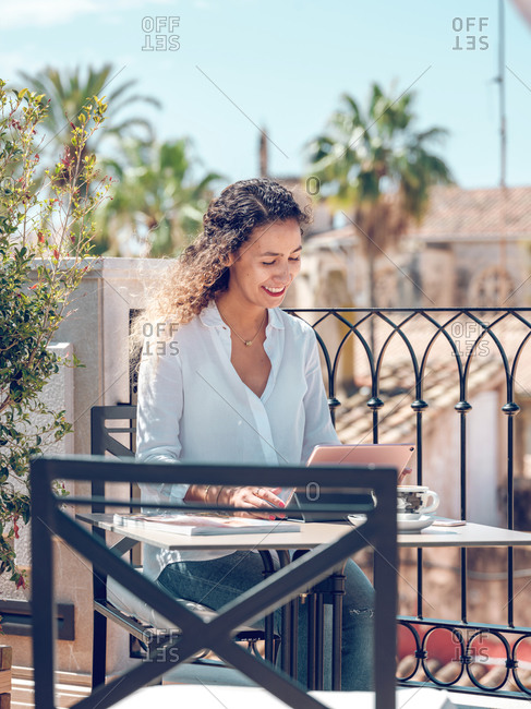 Beautiful young woman charmingly smiling and browsing tablet while sitting at table on terrace of stylish outdoor cafe on sunny day