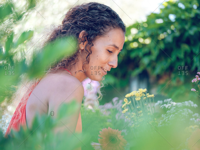 Side view of charming young lady cheerfully smiling and looking away while standing near amazing flowers