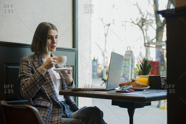 thoughtful female freelancer typing on netbook with blank screen while sitting at table with cup of hot drink and copybook in cafeteria near large window